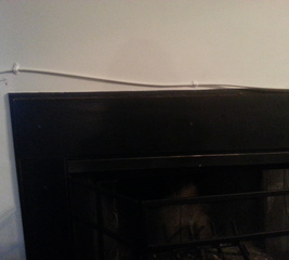 Tack a cable chord to the wall and over the fireplace