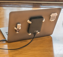 Tech accessories attached to the back of a laptop screen with Sugru clips