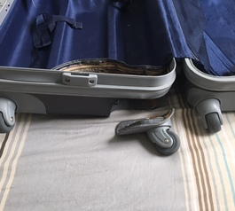 Reattach the spinning feet on as hard-case luggage by using Sugru (before)