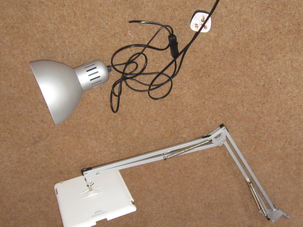 Lamp arm joined to iPad, lamp head next to stand