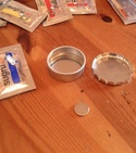 Packets of Sugru next to two metal tins and a magnet