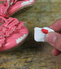 Red and white Sugru being held next to damaged shoe