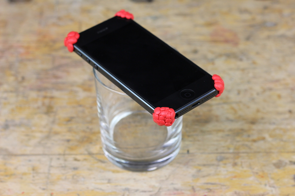 Sugru bumpers on phone being held by a glass