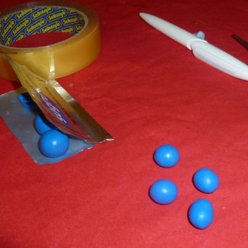 Packet of Sugru and four balls of Sugru on a table with sellotape