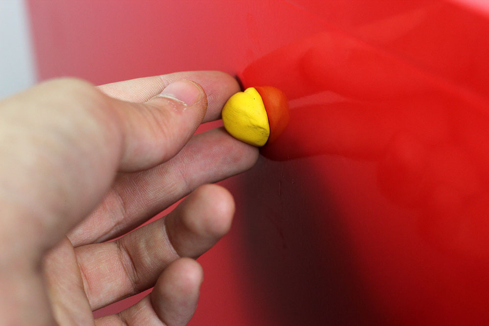 Sugru being smoothed into a ball on the wall